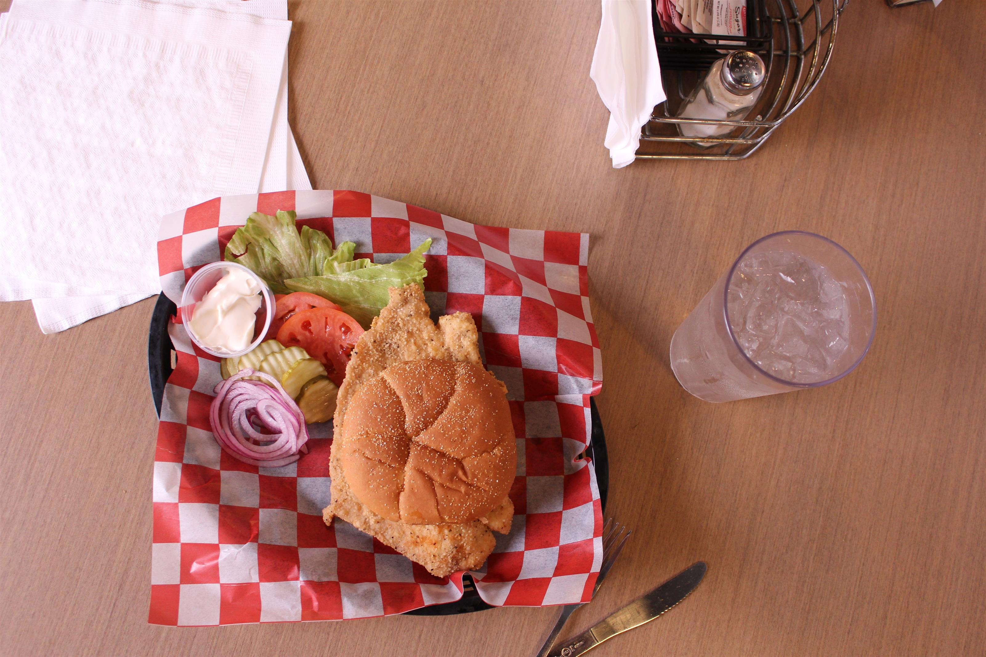 fried chicken sandwich with greens to the side