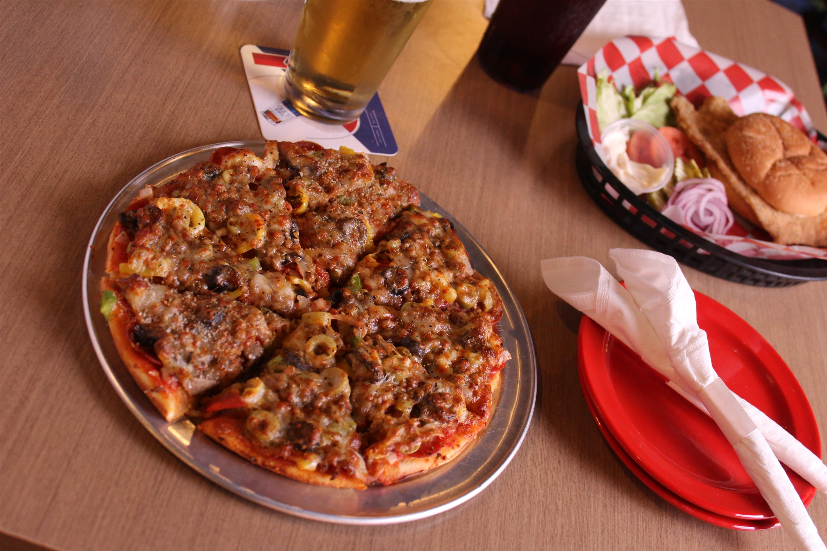 slice pizza pie with beer glass and fried chicken sandwich