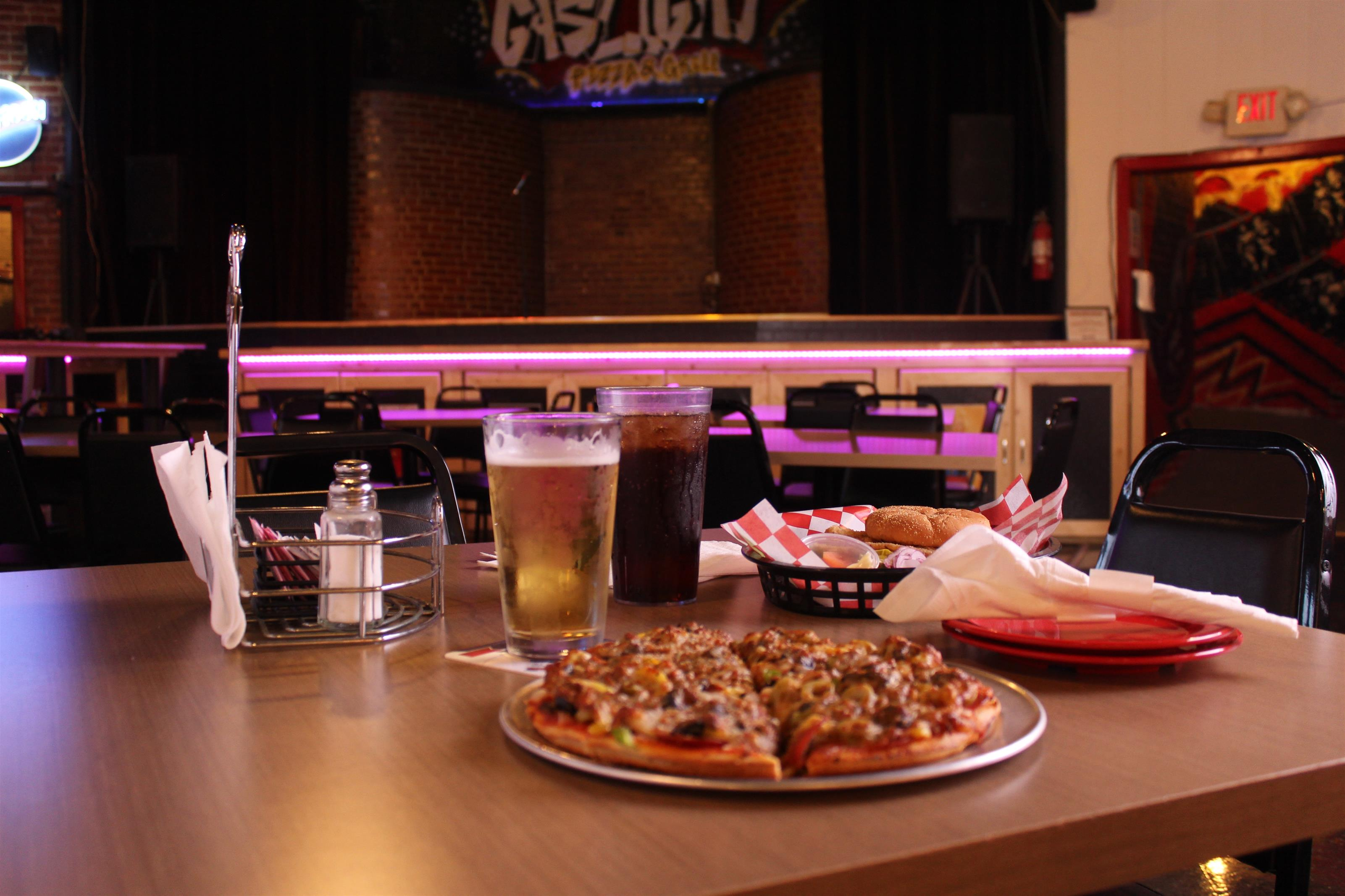 pizza pie with cola and beer in front of stage
