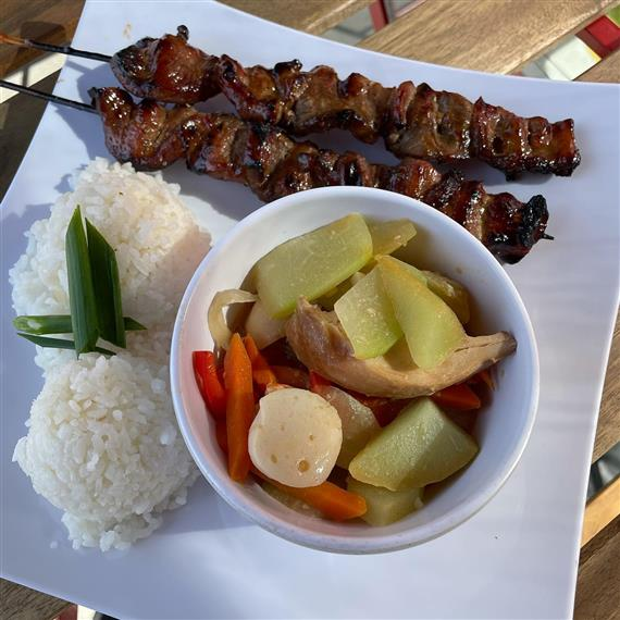 bbq meat on a stick with rice and vegetables