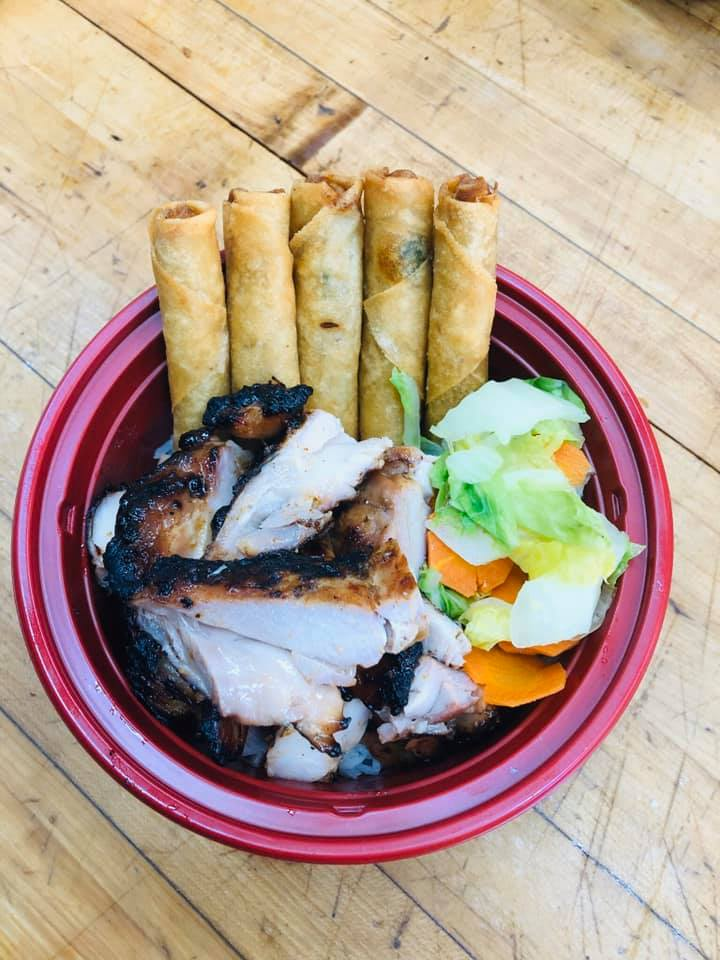bowl of meat with vegetables and egg rolls
