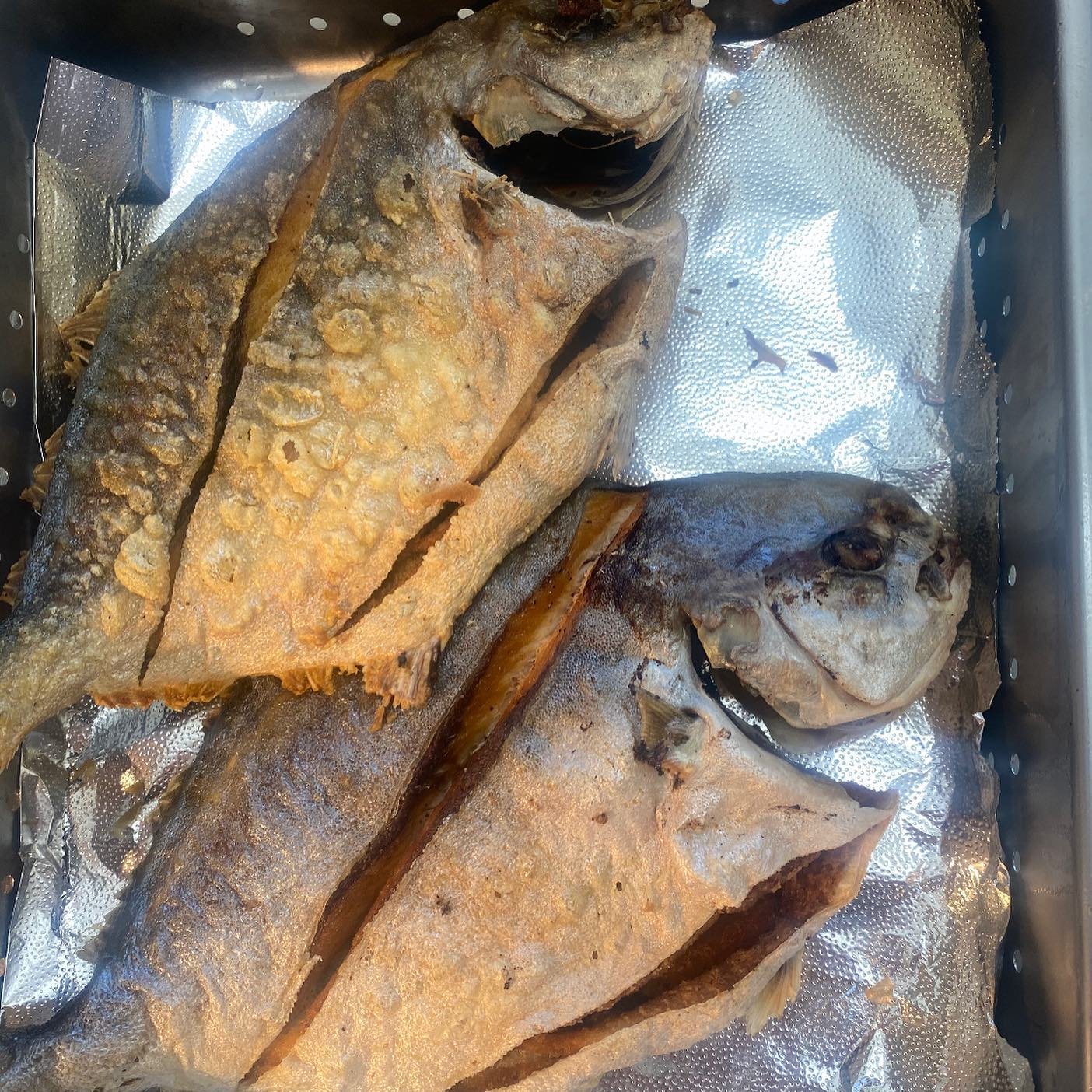 two whole cooked fish on a tray