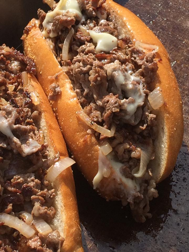 two cheesesteaks with onion on a grill
