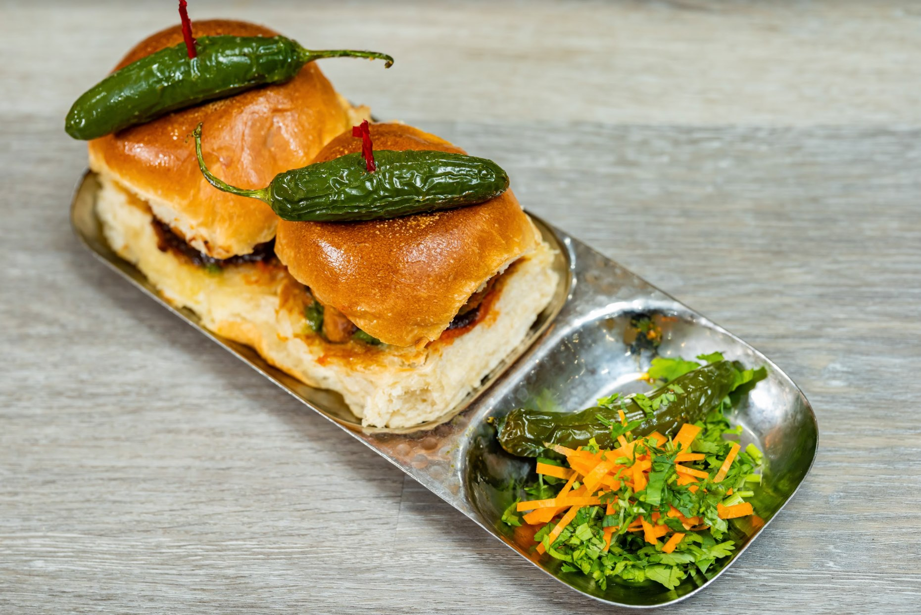 two deep-fried potato patty's coated is served sandwiched between a soft bread bun with tangy tamarind chutney and spicy coriander chutney