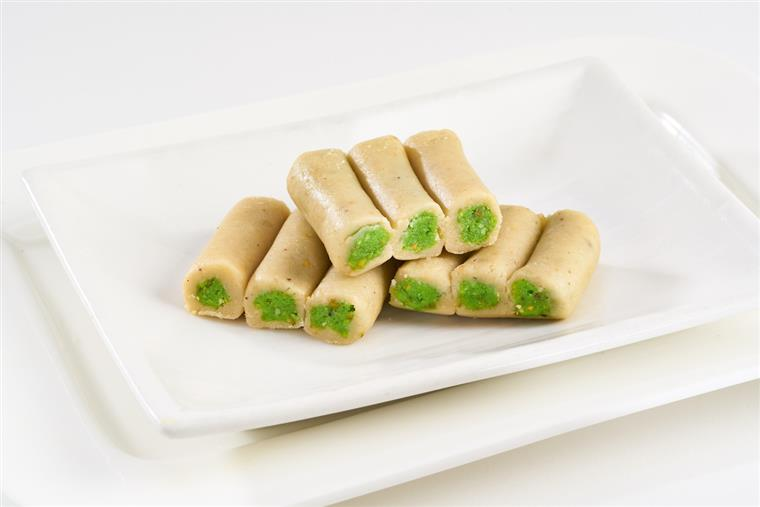 assortment of  Croquette shape mithai made from sweetened cashew paste filled with pistachios