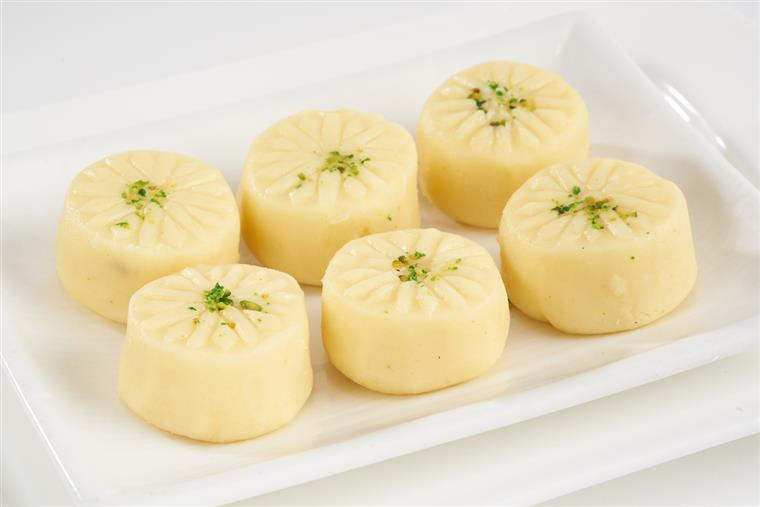 assortment of Solidified milk mini buns garnished with crumbled pistachios