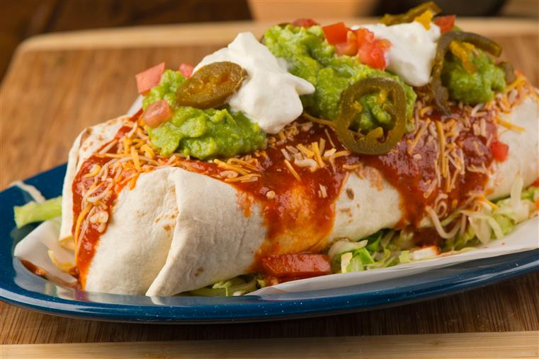 wet burrito topped with sour cream and guacamole