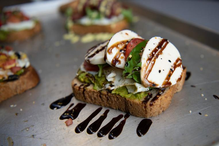 Caprese AvocadoToast: Avocado spread, heirloom tomato, buffalo mozzarella, fresh basil, topped with an over medium local free range egg, and drizzled with balsamic reduction on multi grain
