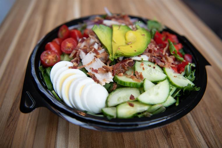 Cobb Salad: Onions, eggs, bacon,cucumbers, tomatoes, roasted red peppers, blue cheese crumbles, avocado, antibiotic free chicken, Greek yogurt ranch