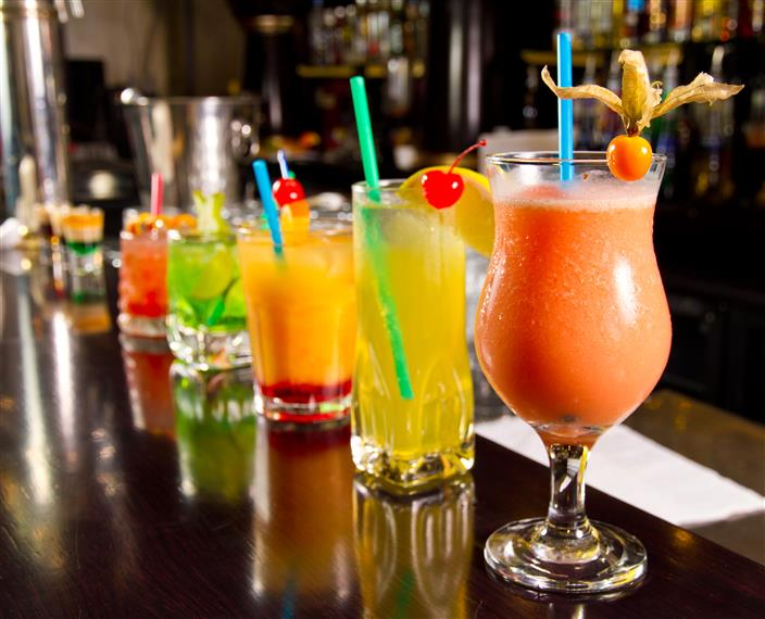 various mixed drinks different colors and sizes on bar lined up in a row