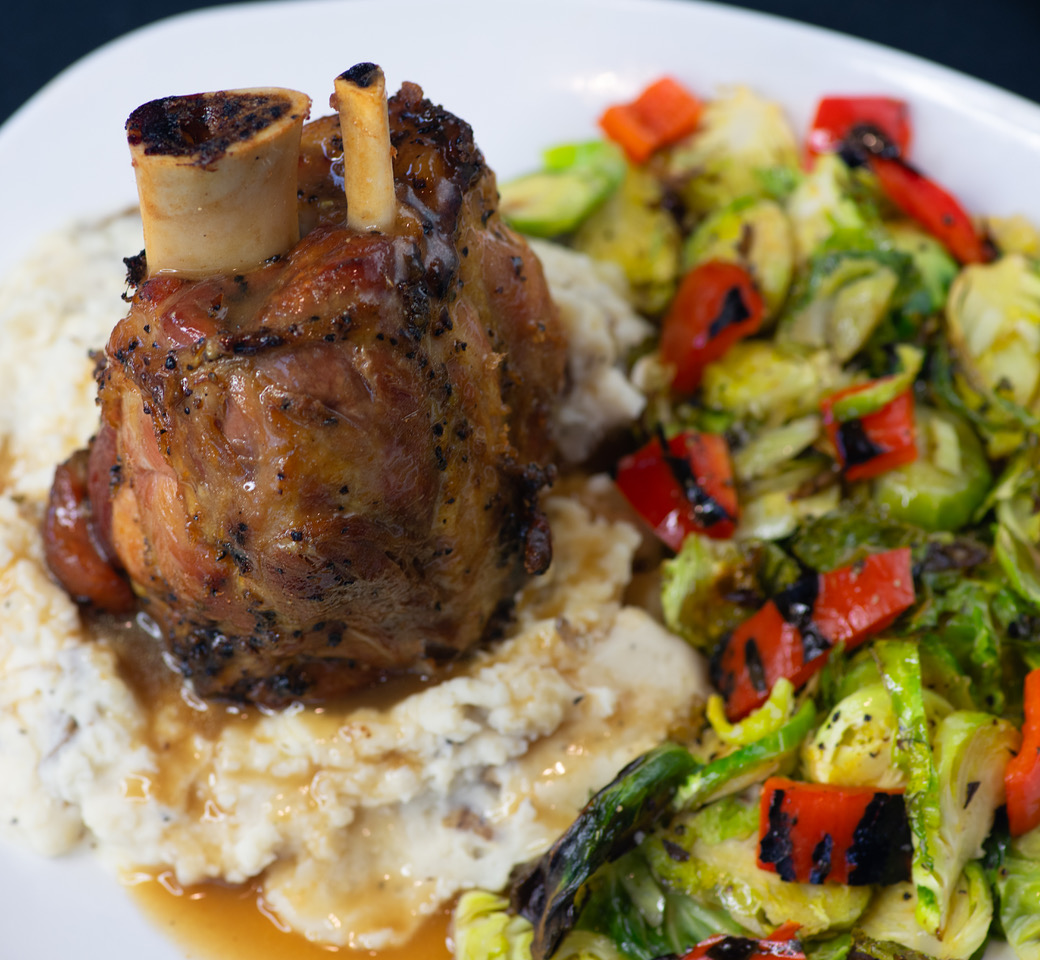 Ossobucco on top of mashed potatoes with a side of assorted vegetables