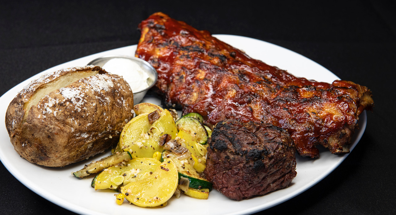 barbeque ribs, steak, baked potato with sour cream on the side and veggies
