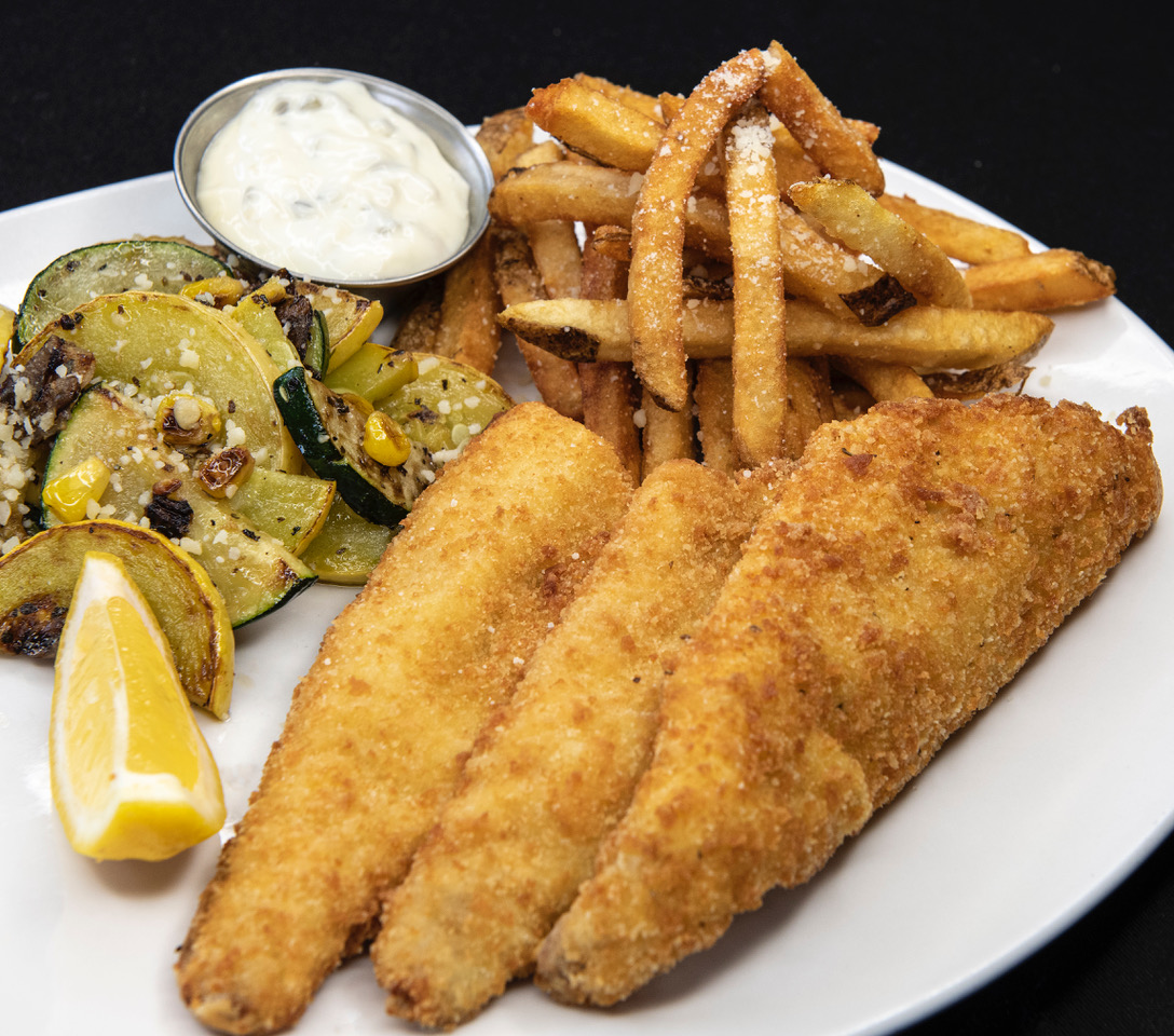fried fish with tartar sauce, fries, and veggies with a lemon wedge