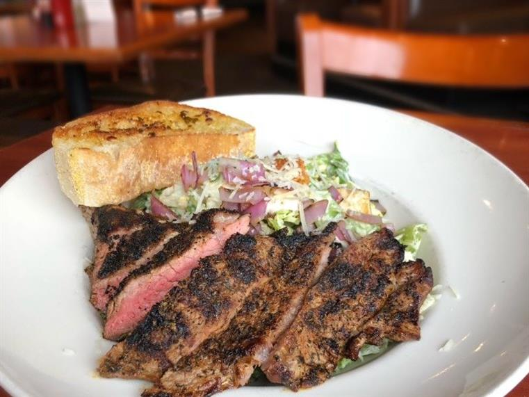 sliced steak over a chopped salad with a side of toasted bread