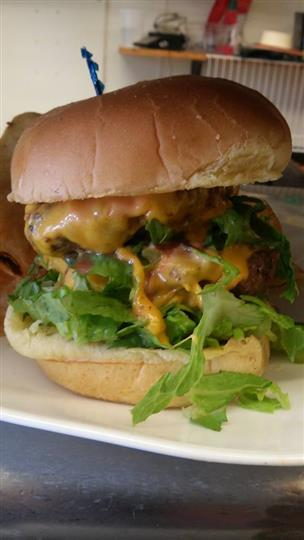 A burger with melted cheese, tomato and lettuce