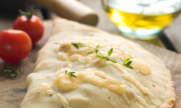 baked calzone with cheese on a wooden board with whole tomatoes on the side
