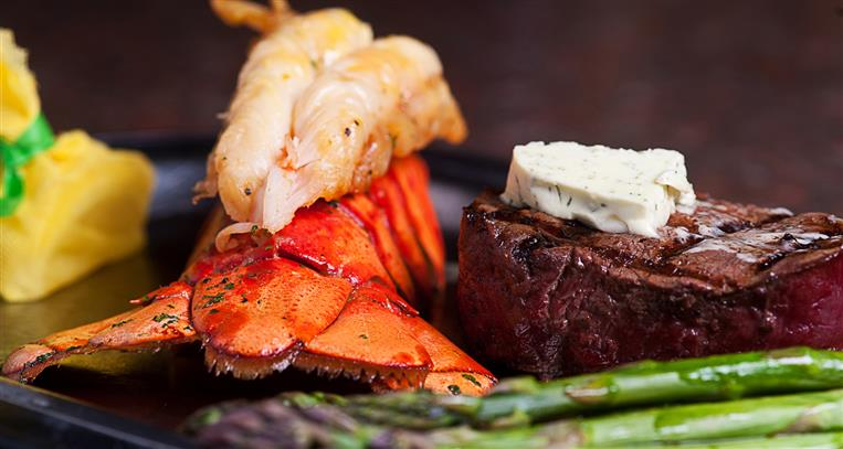 Lobster tail and steak with asparagus on black plate.