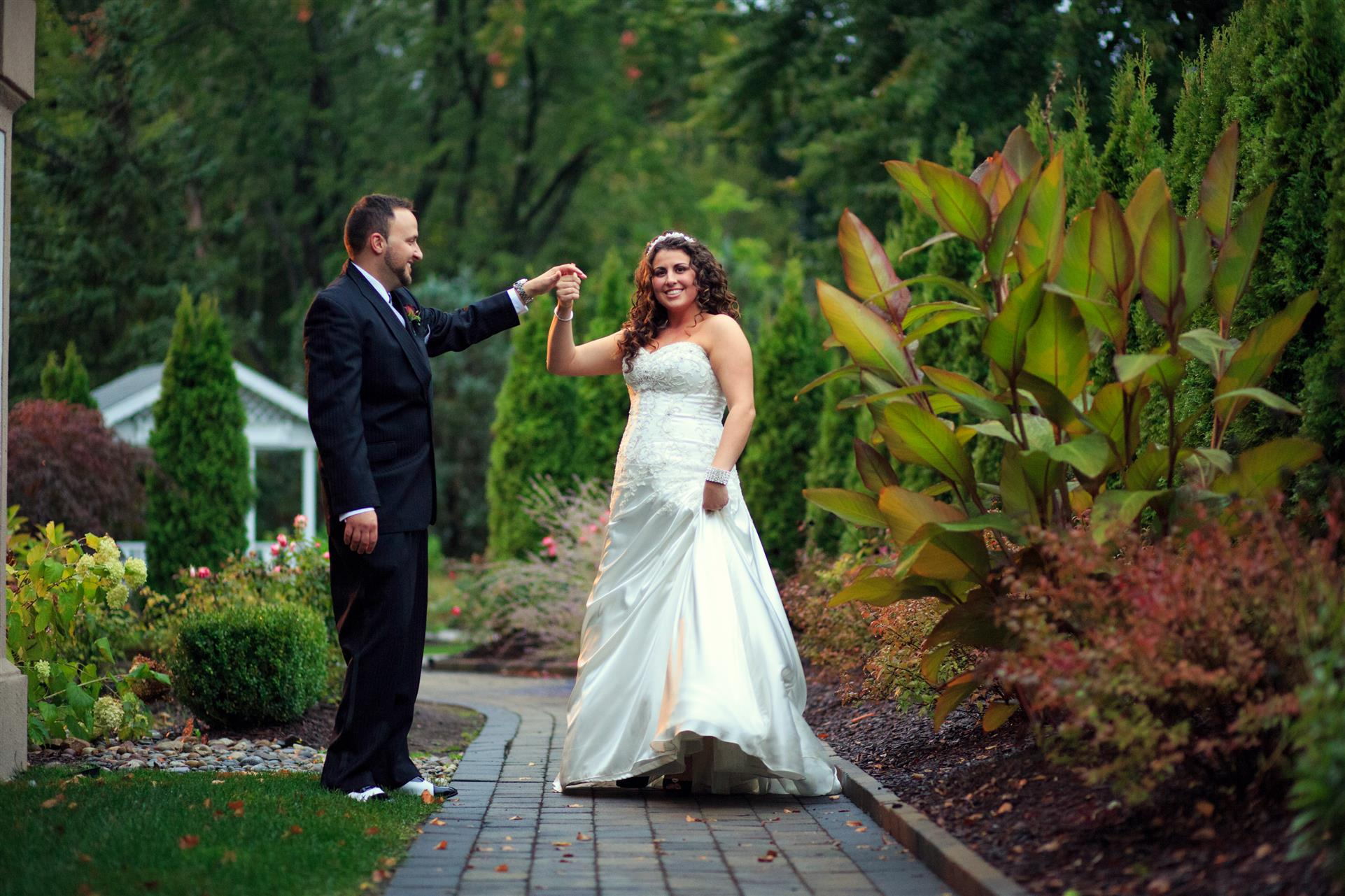 Bride and groom holding hands on walkway