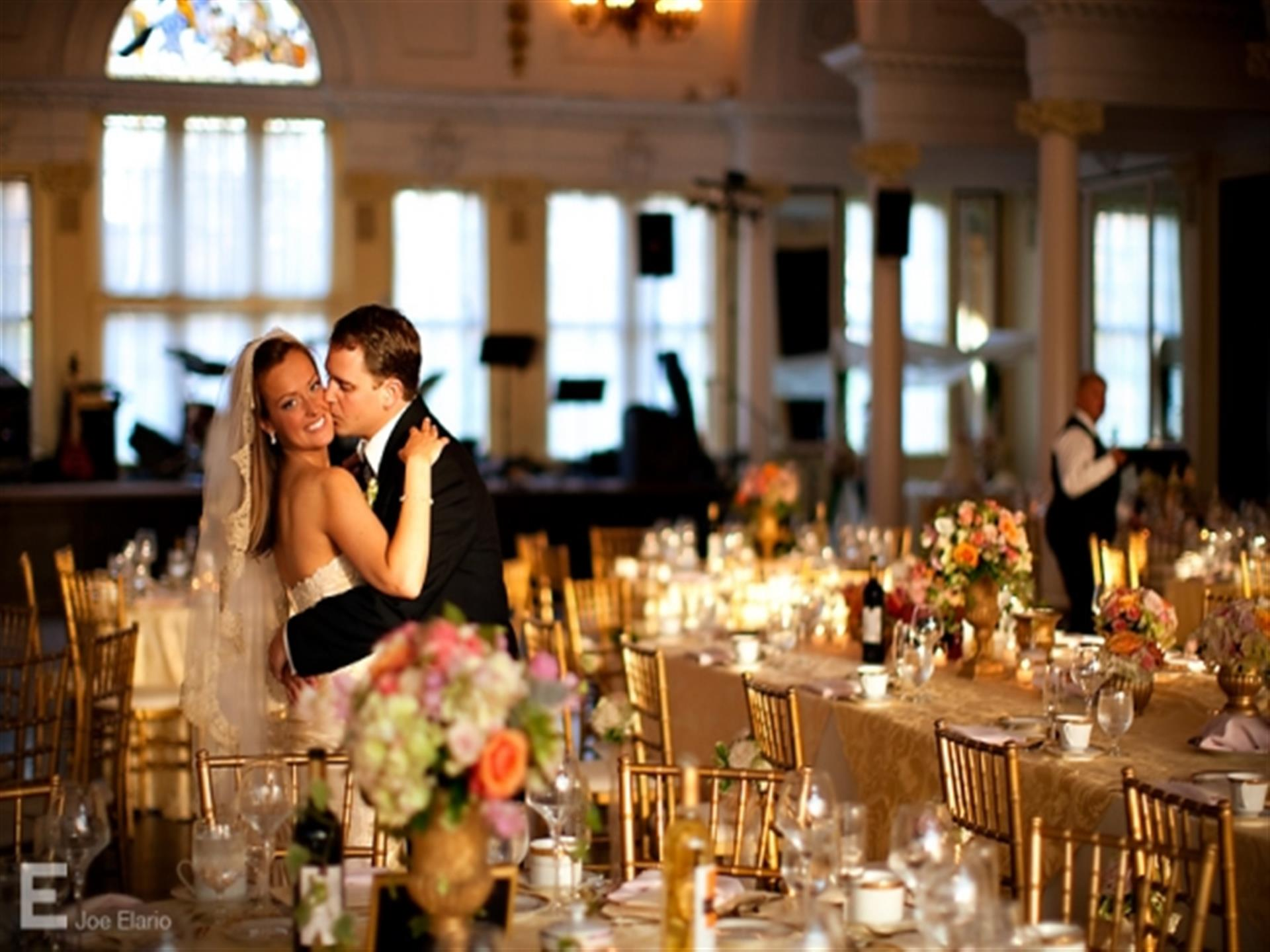 Husband and wife embracing in banquet hall in between covered tables