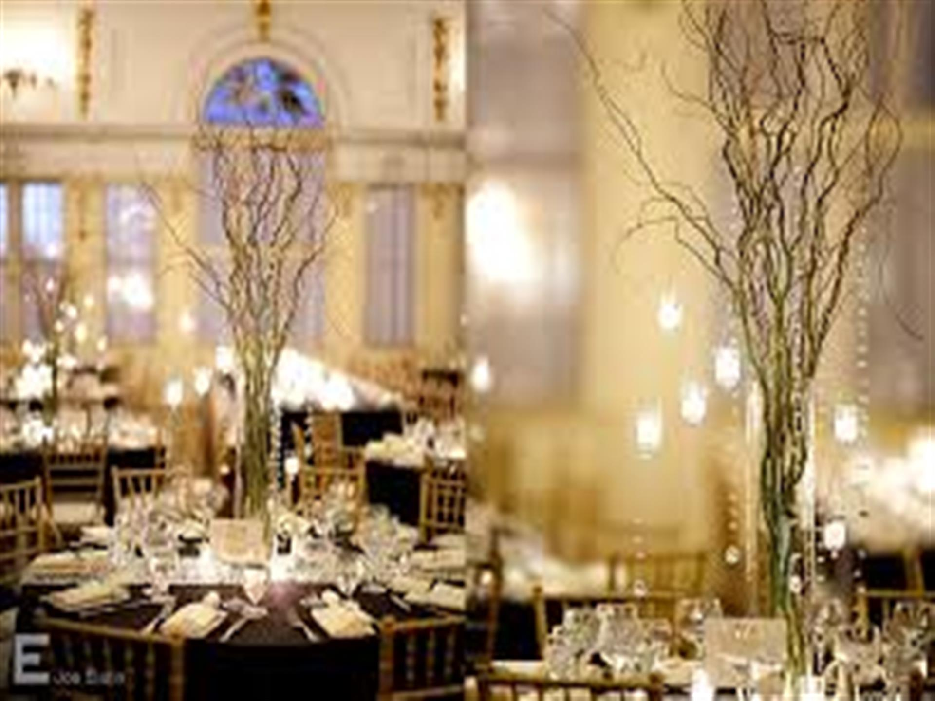 Covered banquet tables with tall, vine centerpieces