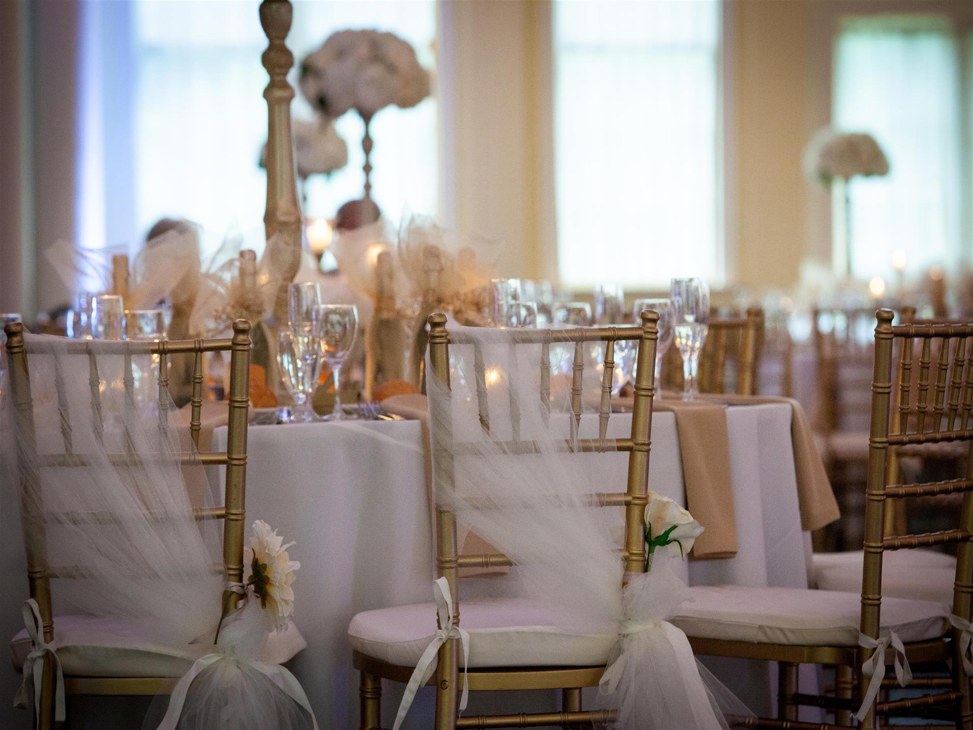White-clothed banquet tables with tulle over banquet chairs