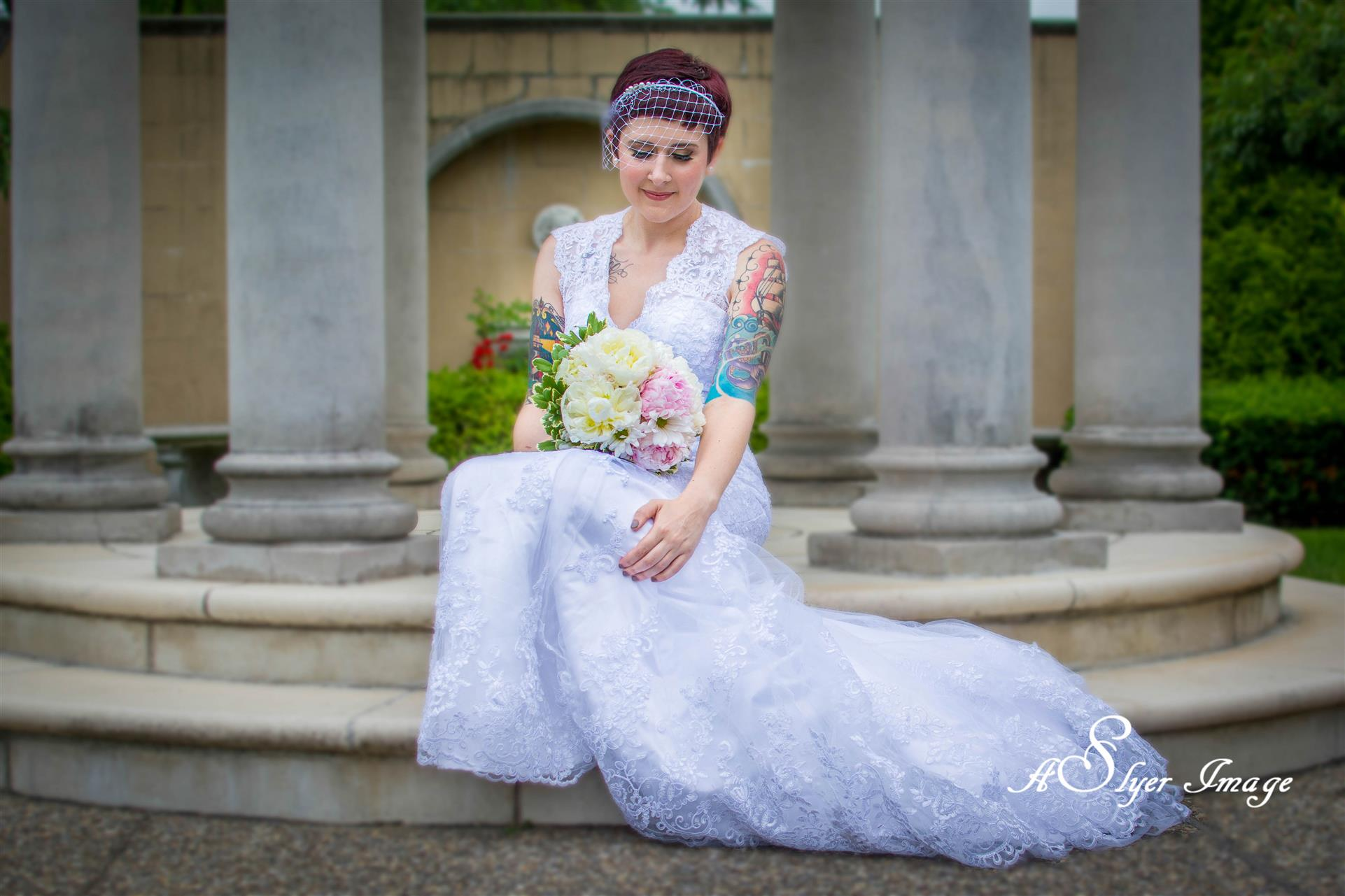 Bride holding bouquet on steps in front of columns