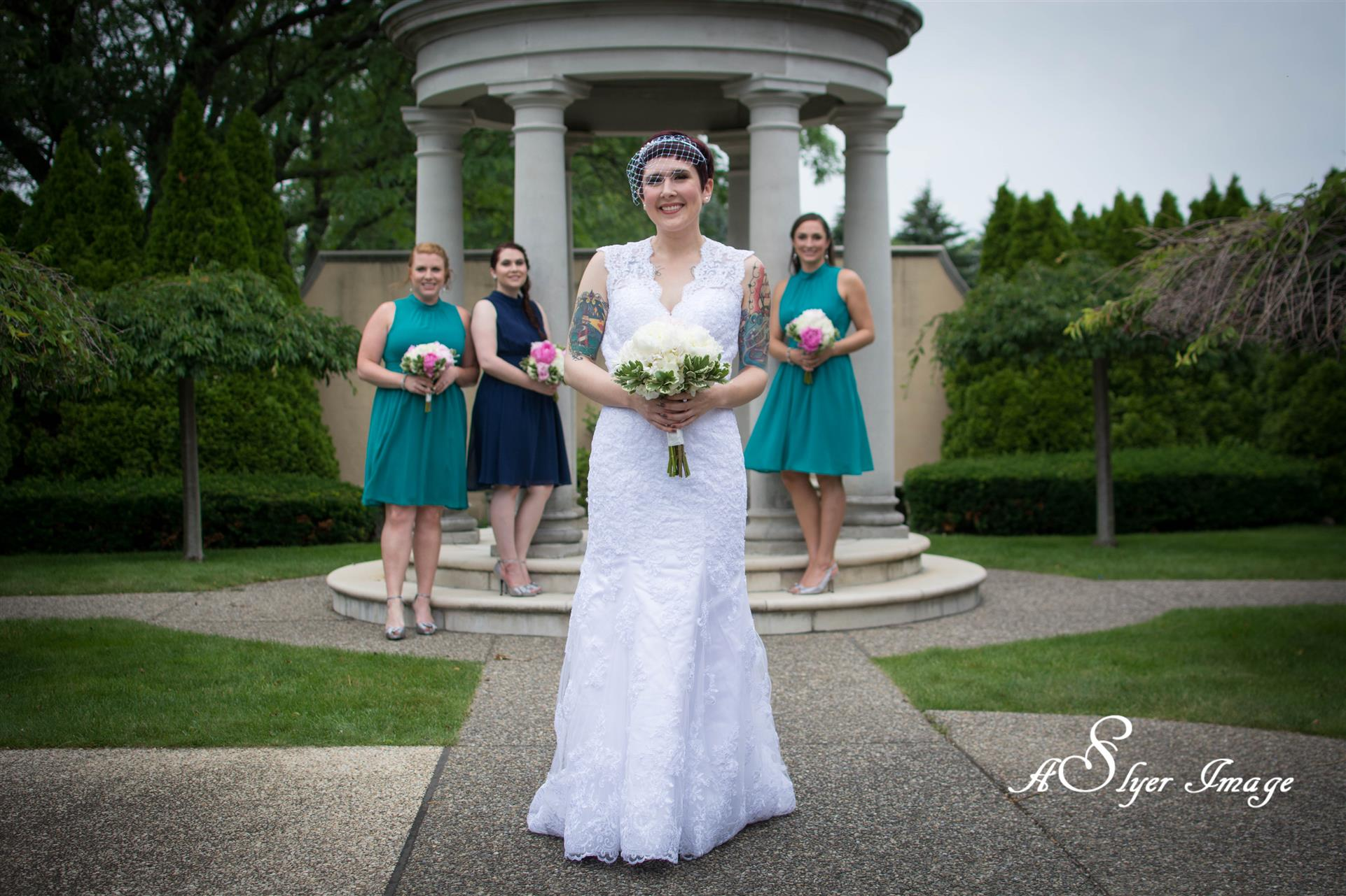 Bride and bridesmaids holding bouquets in front of columned structure