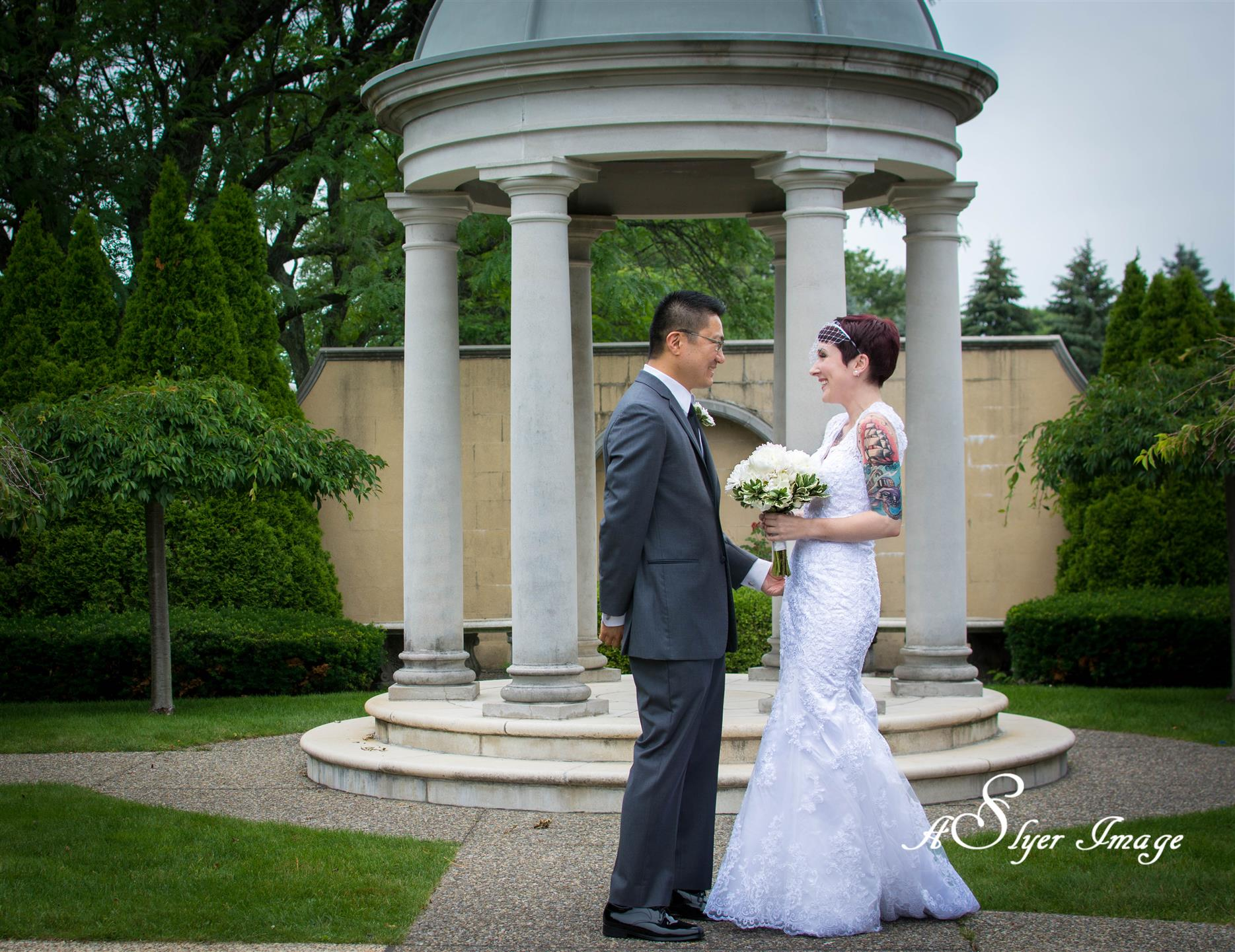 Bride and groom gazing at eachother in front of columned structure