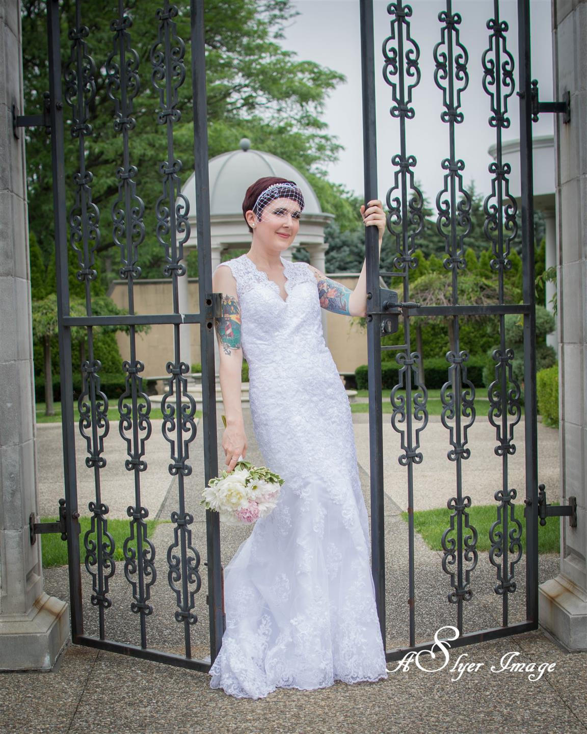 Bride holding bouquet standing in open gateway