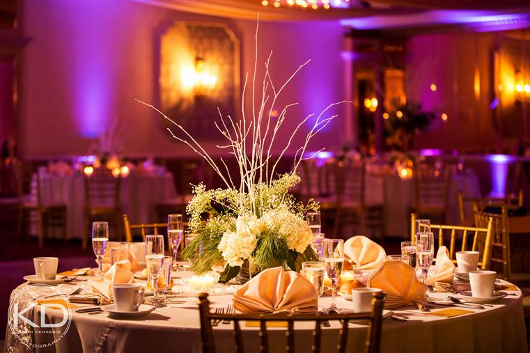 White-clothed table with placesettings in room with other banquet tables under gold and purple lighting