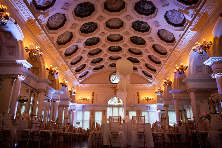 White-clothed tables in banquet room with high ceilings