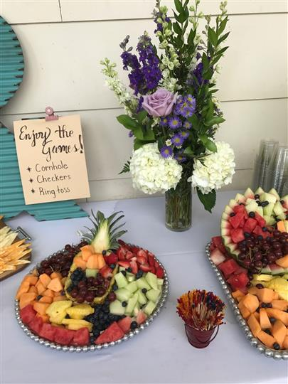 fruit platter, flowers, toothpicks, and a sign on a table