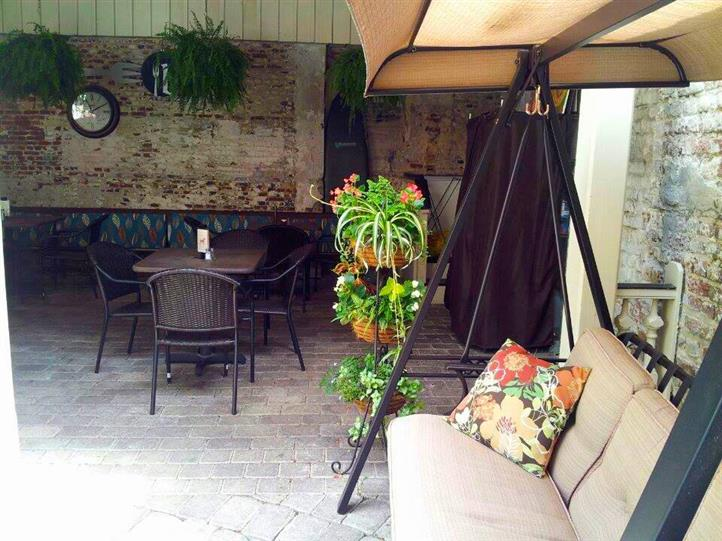 outside dining area with tables, chairs and a couch swing