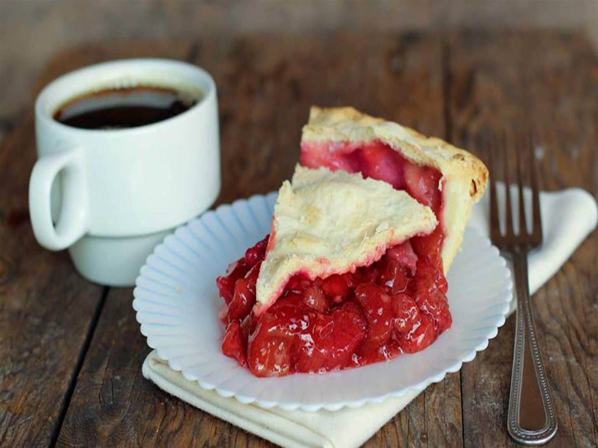 baked cherry pie slice on a plate with a cup of coffee