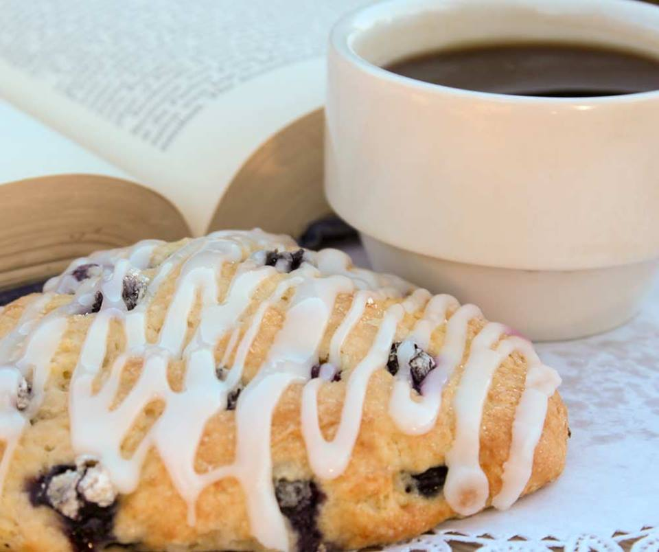 baked blueberry scone with a cup of coffee on the side