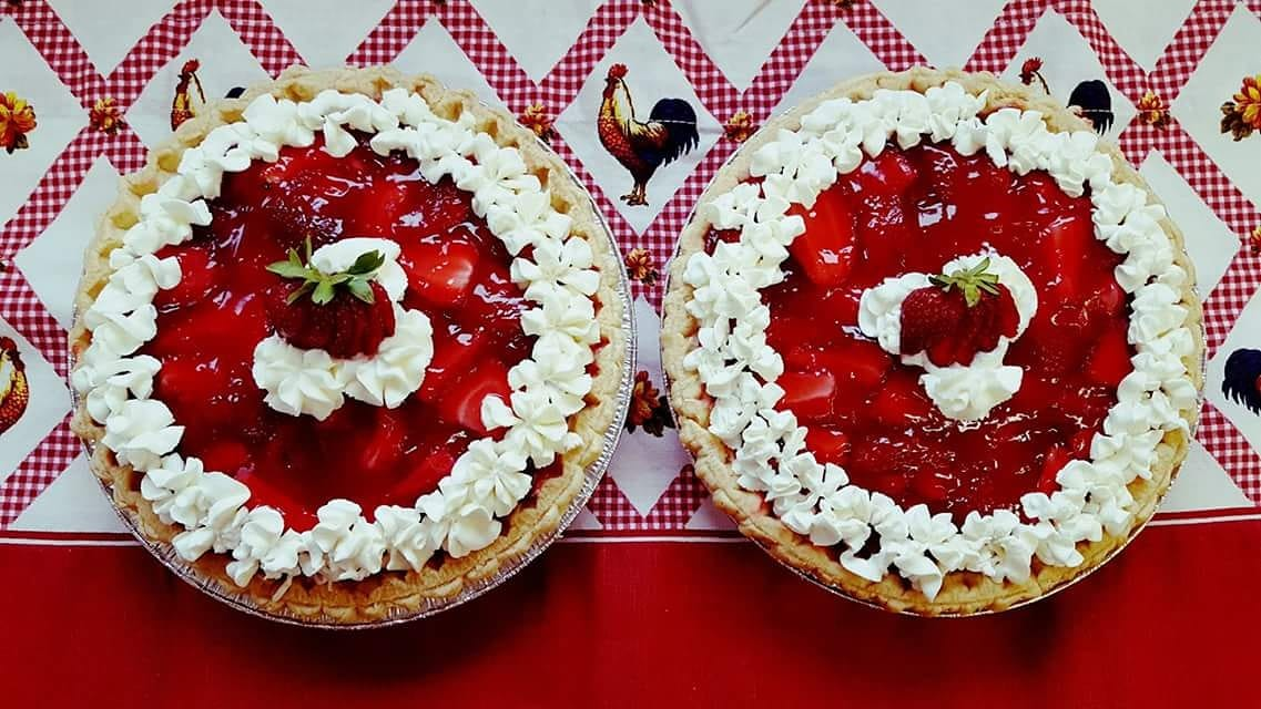 two baked strawberry pies with whipped cream