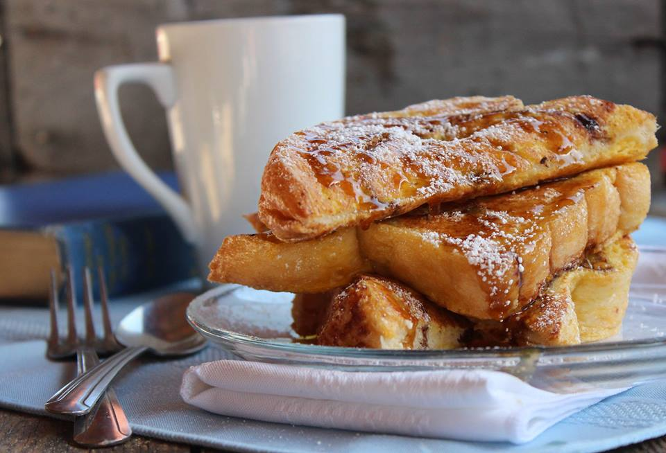 baked french toast on a plate with a cup of coffee on the side