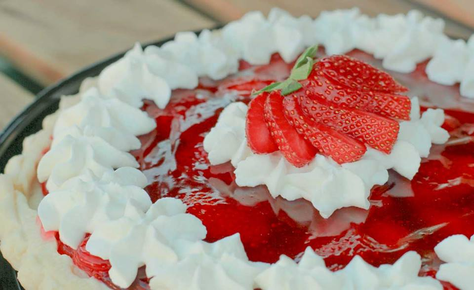 open baked strawberry pie with whipped cream