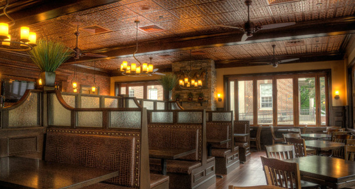 Dining room with seating booths, tables, chairs. Patterned tile ceiling.