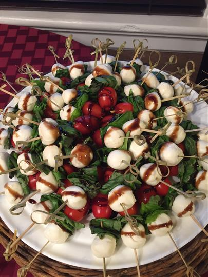 platter filled with mozzarella balls on skewers with tomatoes and spinach