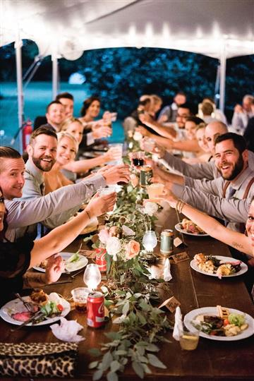large table of people smiling at the camera making a toast