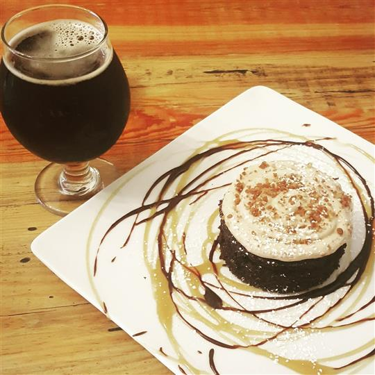 decorated dessert with syrup with a glass of craft beer