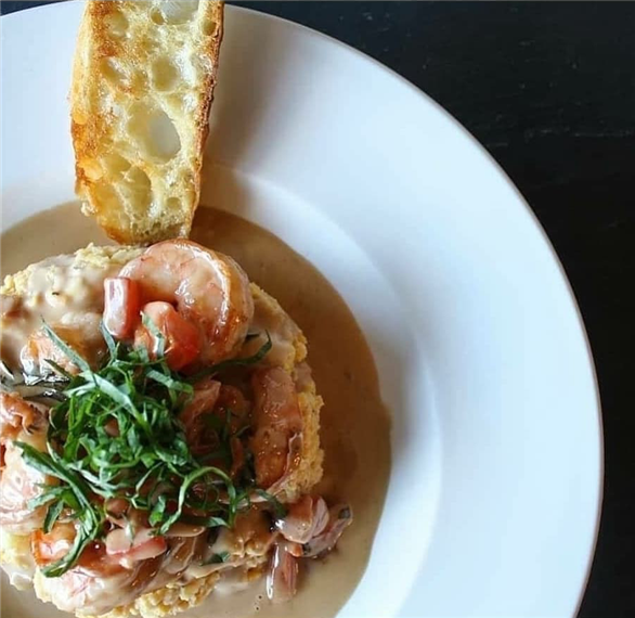 Risotto topped with a creamy sauce, shrimp, basil shreds, and a slice of toasted bread on the side.