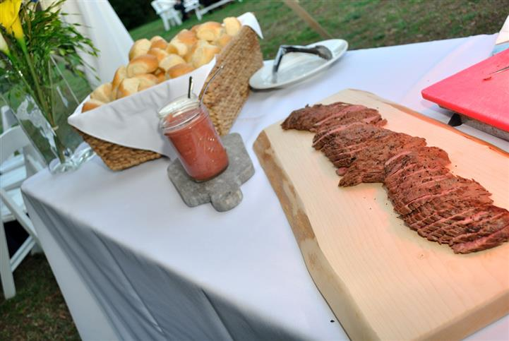 catering buffet outdoors with sliced steak and break