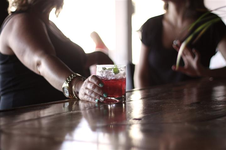 two woman sitting at a bar holding a mixed cocktail