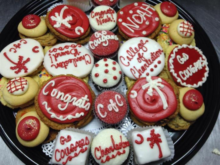 Several cookies topped with red and white decoration and letters
