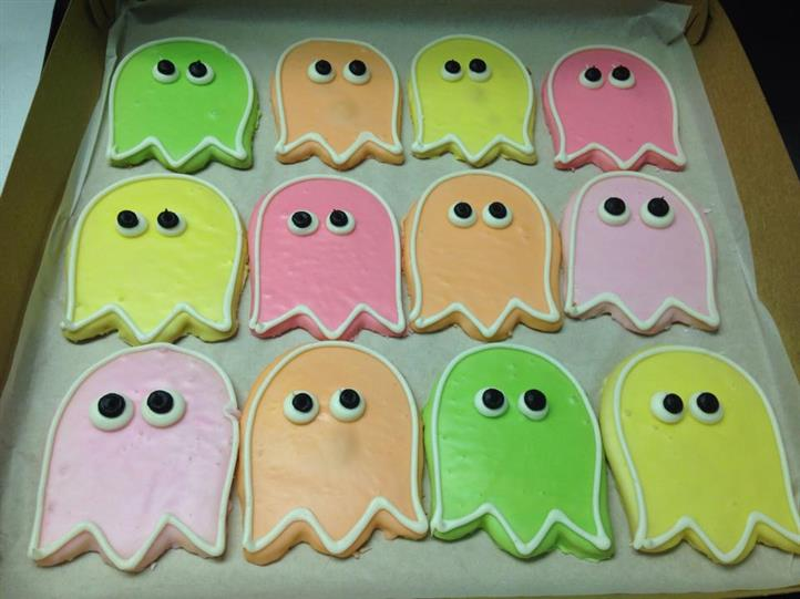 Covered cookies in several colors in the shape of ghost