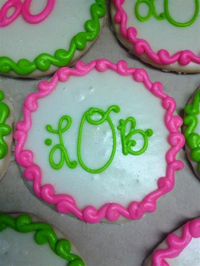 White covered cookies decorated with pink and green letters