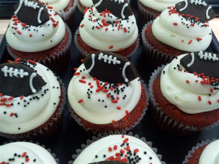 Cupcakes topped with white chocolate and a dark chocolate football ball