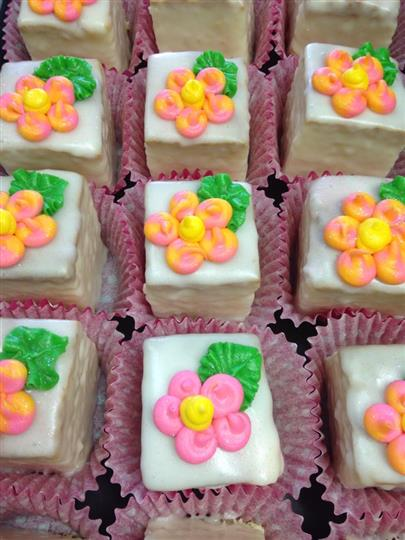 White mini cakes topped with flowers in several colours